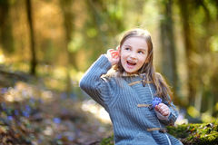 采摘春天的第一朵花可爱的小女孩在森林 免版税库存图片