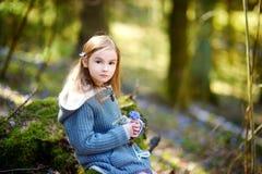 采摘春天的第一朵花可爱的小女孩在森林 库存照片