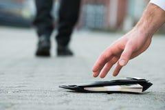 采摘有金钱的商人下落的钱包 免版税库存图片