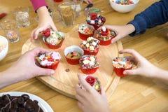 采摘杯形蛋糕的孩子在表上 库存照片