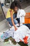 采摘肮脏的衣裳的妇女在洗衣店 免版税库存照片
