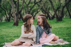 采摘花的两个愉快的矮小的女朋友在春天庭院里 一起花费时间的姐妹室外 免版税库存照片