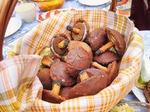 采蘑菇在篮子的巧克力糖假日快餐曲奇饼欢乐食物在桌野餐宴餐户外 库存图片