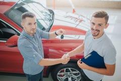 采购员和经销商站立并且互相震动` s手 卖主把握从汽车的关键 两个在照相机查寻 他们是 库存图片