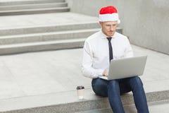 采购 圣诞老人帽子工作的姜人室外 库存照片