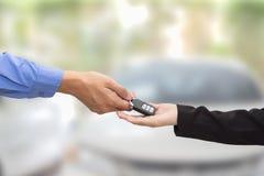 采购的汽车 给一辆关键汽车的商人迷离的女实业家 免版税库存照片