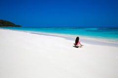 释放在异乎寻常的海滩的少妇实践的瑜伽与蓝色w 免版税库存图片