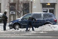 释放汽车的人铁锹从雪 库存照片
