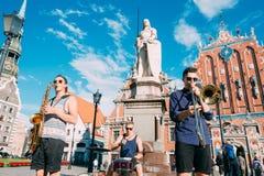 里加拉脱维亚街音乐三重奏带,弹奏为捐赠的三个年轻人仪器在市政厅广场 库存照片