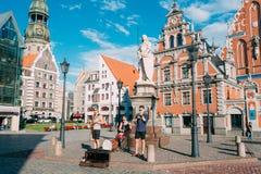 里加拉脱维亚街音乐三重奏带,弹奏为捐赠的三个年轻人仪器在市政厅广场 免版税库存照片