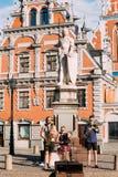 里加拉脱维亚街音乐三重奏带,弹奏为捐赠的三个年轻人仪器在市政厅广场 库存图片
