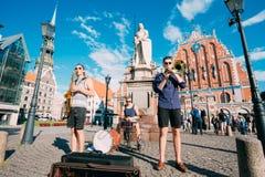 里加拉脱维亚街音乐三重奏带,弹奏为捐赠的三个年轻人仪器 库存图片