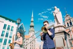 里加拉脱维亚街音乐三重奏带,演奏Ins的三个年轻人 免版税图库摄影