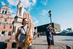 里加拉脱维亚街音乐三重奏带,演奏Ins的三个年轻人 免版税库存照片