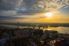 里加,拉脱维亚:城市、全景河和在日落的桥梁的顶视图 图库摄影