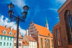 里加,拉脱维亚- 2017年5月06日:位于在色的舒适老房子的看法,街灯和教会 免版税图库摄影