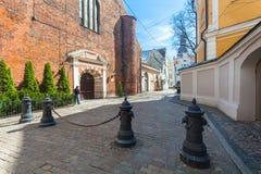 里加,拉脱维亚- 2017年5月06日:位于城市铈在色的舒适老房子的看法,教会和狭窄的老街道 库存图片