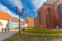 里加,拉脱维亚- 2017年5月06日:位于市中心的在色的舒适老房子的看法和教会 免版税库存图片