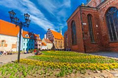 里加,拉脱维亚- 2017年5月06日:位于里加的市中心在色的舒适老房子的看法和教会 库存图片