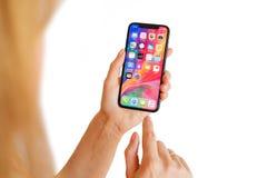 里加,拉脱维亚- 2018年3月15日:使用最新的一代iPhone x的妇女 免版税库存图片