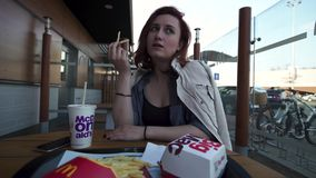 里加,拉脱维亚- 2019年4月22日:吃在便当餐馆Mcdonalds -巨无霸、中等油炸物和古柯的年轻女人 股票录像