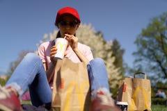 里加,拉脱维亚- 2019年4月28日:吃McDonalds巨无霸汉堡cheesburger和喝古柯的成功的女商人 库存图片