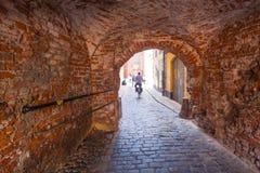 里加,拉脱维亚- 2017年5月06日:在老砖曲拱和人的看法位于城市分的自行车的 库存图片