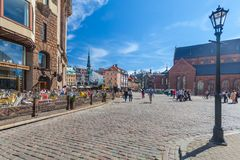 里加,拉脱维亚- 2017年5月06日:在色的舒适老房子的看法,教会和圆顶摆正与是被找出的i的街道咖啡馆 免版税库存图片