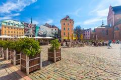 里加,拉脱维亚- 2017年5月06日:在色的舒适老房子的看法,教会和圆顶摆正与是被找出的i的街道咖啡馆 库存照片