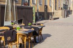 里加,拉脱维亚- 2017年5月06日:在街道咖啡馆或餐馆空的桌上的看法位于里加的市中心 图库摄影