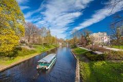 里加,拉脱维亚- 2017年5月06日:在运河有游舫的和松弛人的看法银行的在公园Bastio 库存照片