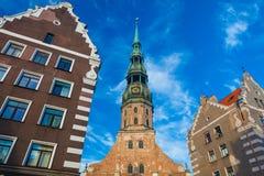 里加,拉脱维亚- 2017年5月06日:在里加` s StPeter ` s教会的看法,餐馆、咖啡馆和最近的房子位于Th 图库摄影