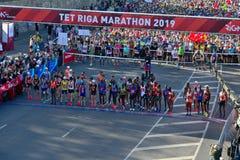 里加,拉脱维亚- 2019年5月19日:起初排队线的里加泰特马拉松的精华赛跑者 库存照片