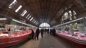 里加,拉脱维亚- 2019年3月16日:里加中央市场肉亭子,买新鲜食品-前策帕林飞艇飞机棚的人们- 股票录像
