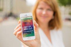 里加,拉脱维亚- 2016年7月14日:显示Pokemon的妇女去电话的网站 Pokemon Go是一基于地点的被增添的现实mobi 库存图片
