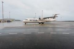 里加,拉脱维亚- 2017年1月24日:有Norra北欧地方航空公司飞机ATR的72-500里加国际机场在背景中 免版税库存图片