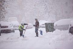 里加,拉脱维亚- 11月4 :供以人员从走道的清洁雪, sno 免版税库存图片