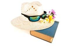 里德帽子、太阳镜、花和书 库存照片