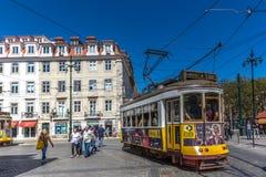 里斯本、葡萄牙- 2018年5月9日-乘坐一辆传统黄色电车的游人和本机在街市里斯本,美丽的蓝天的 免版税库存图片
