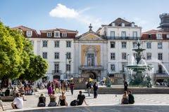 里斯本、葡萄牙- 2018年5月9日-走在一条传统大道的游人和本机在里斯本街市在一蓝天天, Por 免版税库存图片