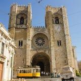 里斯本大教堂门面和通过的电车轨道  免版税库存图片
