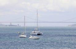 里斯本江边:白色游艇,红色桥梁,贝伦塔 库存照片