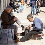 里斯本,葡萄牙:工作在Rossio的擦皮鞋的人 免版税库存图片