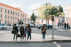 里斯本,葡萄牙01可以2018年:步行者发怒街道 朋友女孩或公司在交叉点站立 免版税图库摄影