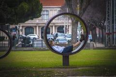 里斯本,葡萄牙- 2018年1月:休息在一条异常的长凳的公园的女孩 库存图片