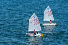 里斯本,葡萄牙- 2010年4月03日:游艇在蓝色海 儿童运动员参加种族在晴天 海航行 库存图片