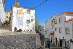 里斯本,葡萄牙- 2017年11月5日:狭窄和五颜六色的街道在有被修补的台阶和街道艺术的Alfama邻里 图库摄影