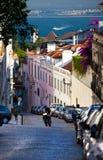 里斯本,葡萄牙- 2011年6月18日:沿狭窄的陡峭的街道的看法到Taxo河的方向里 免版税图库摄影
