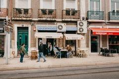 里斯本, 2018年6月18日:一个小组人或朋友在街道坐在餐馆,饮用的酒旁边和 库存图片