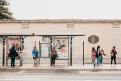 里斯本, 2018年6月18日:公共汽车站等待的运输的青年人 普通的城市生活 库存照片